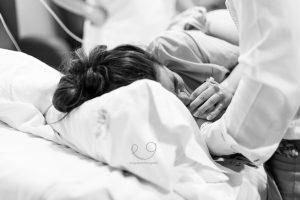 mujer durante una contracción agarrando a su pareja