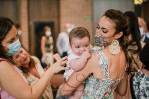 Madre con mascarilla bautizando a un niño