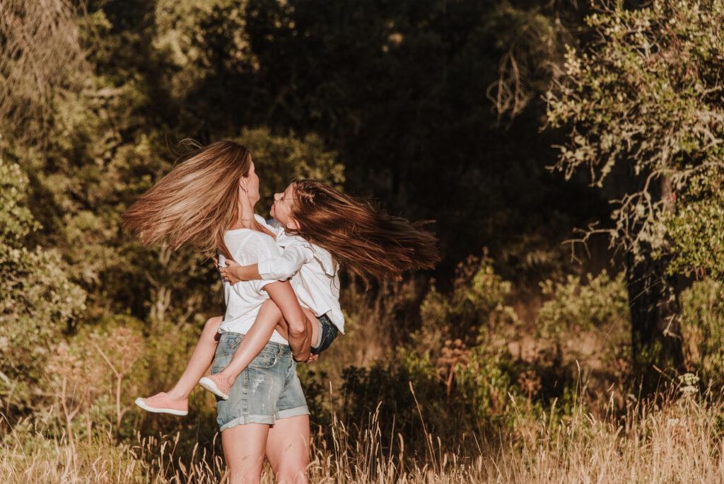 Madre e hija dando vueltas en un bosque al atardecer ©EvaGascon